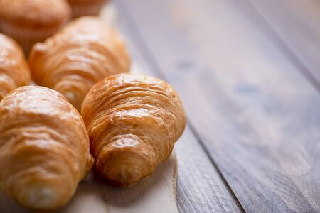 Close-up of croissants fresh out of the oven on wooden board. Banco de Imagens