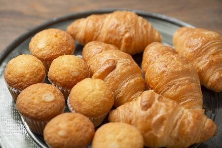 Close-up of cupcakes and croissants on metal tray on brown wooden table. Breakfast.