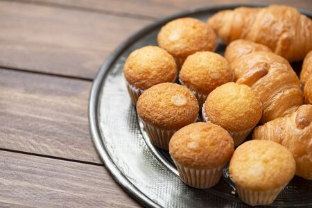 Cupcakes and croissants on metal tray on brown wooden table. Copy space.