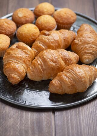 Cupcakes and croissants on metal tray on brown wooden table. Banco de Imagens