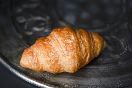 Croissant on metal tray. Breakfast.