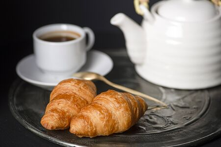 Croissants next to coffee cup and ceramic coffee pot on metal tray. Breakfast. Banco de Imagens