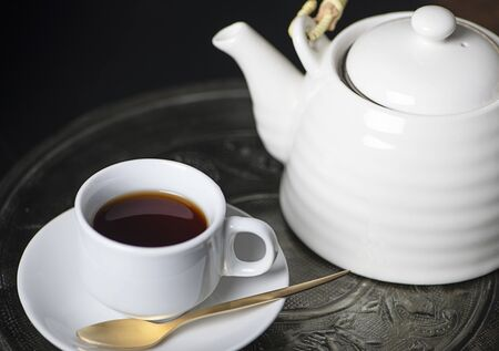 Coffee cup and ceramic coffee pot on metal tray. Breakfast. Banco de Imagens