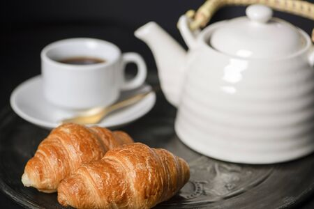 Croissants and cup of coffee next to coffee pot on metal tray. Breakfast. Banco de Imagens