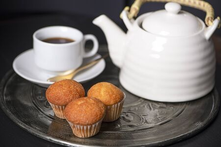 Cupcakes next to cup of coffee maker on metal tray. Banco de Imagens