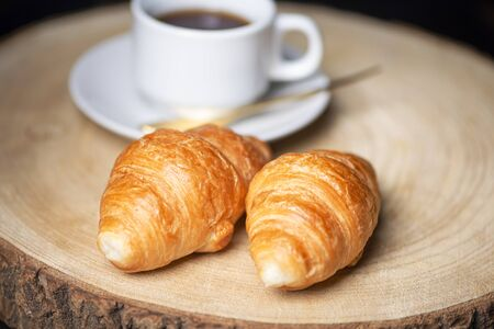 Close-up of two croissants next to cup of coffee on wooden board. Banco de Imagens