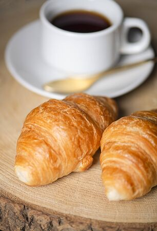 Two croissants next to cup of coffee on wooden board.