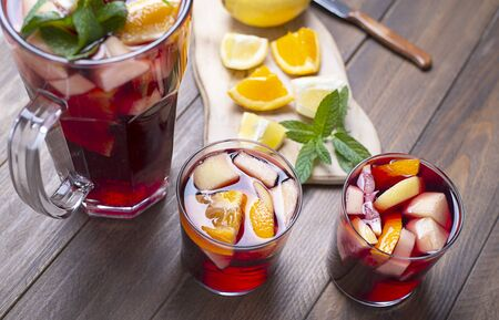 Two glasses and a pitcher with sangria and fruit next to cut lemon and orange on a wooden background. Sangria, a typical Spanish refreshing wine drink.