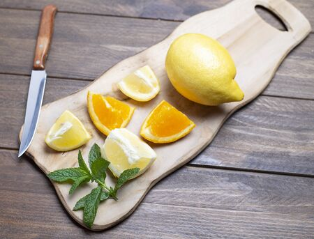 Cut lemon and orange on wooden board next to a knife on brown wooden table. Banco de Imagens