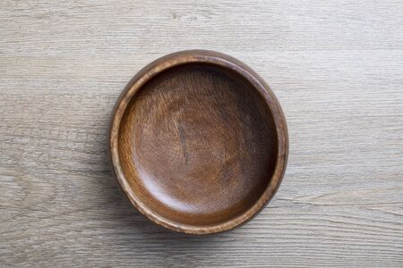 Top view of brown wooden bowl on gray wooden table. Traditional rustic bowl.