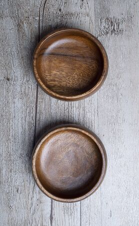 Top view of two brown wooden bowls on gray wooden table. Traditional rustic bowl.