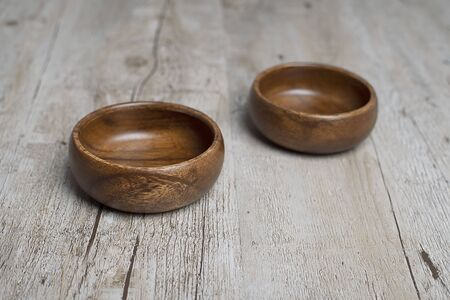 Two brown wooden bowls on gray wooden table. Traditional rustic bowl.