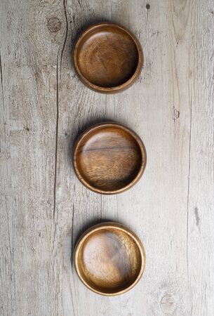 Three brown wooden bowls on gray wooden table. Traditional rustic bowl. Banco de Imagens