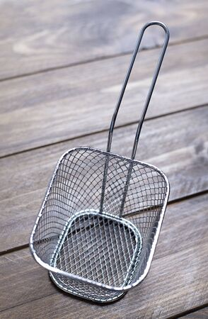 Metallic basket for frying french fries on brown wooden table. Banco de Imagens