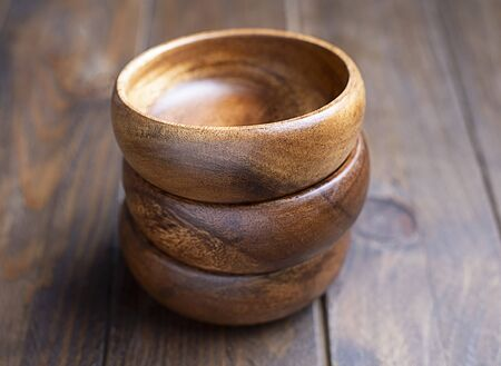 Close-up of three brown wooden bowls stacked on brown wooden table. Traditional rustic bowl.
