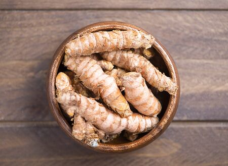Turmeric roots in a wooden bowl on brown wooden table.