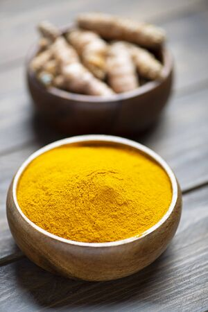 Bowl with curcumin powder in the foreground next to another bowl with turmeric root on brown wooden table. Spice for health and ingredient of Indian cuisine. Banco de Imagens