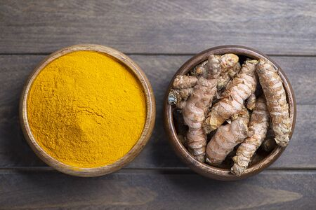 View from above bowl with turmeric powder next to another bowl with turmeric root on brown wooden table. Spice for health and ingredient of Indian cuisine. Stock Photo