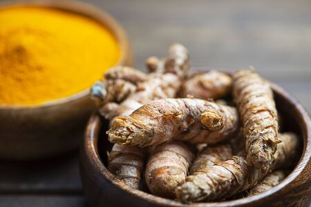Bowl with turmeric root in the foreground next to bowl with turmeric powder on brown wooden table. Spice for health and ingredient of Indian cuisine. Stock Photo
