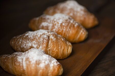 Croissants with sugar on top on wooden board. Sweet for breakfast. Stock Photo
