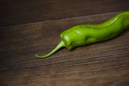 Green pepper on brown wooden table.