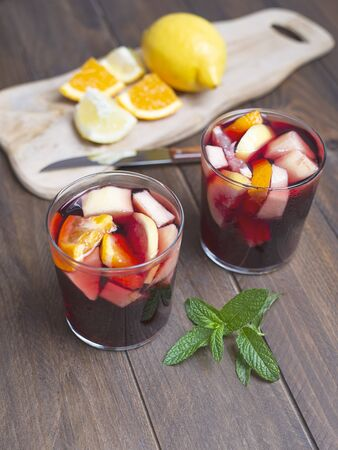 Two glasses and with sangria and fruit next to cut lemon and orange on a wooden background. Sangria, a typical Spanish refreshing wine drink. Stock Photo