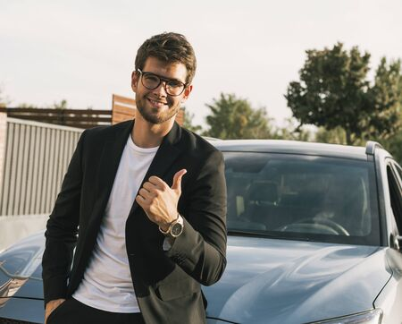 Close-up of attractive young man with beard and glasses in suit is leaning on his car looks at the camera.suit Stock Photo