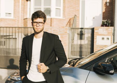 Close-up of attractive young man with beard and glasses in suit is leaning on his car.