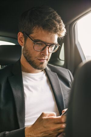 Young and attractive man with a beard and glasses is reading inside a car. Business
