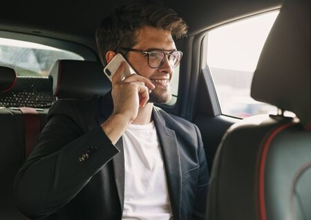 Young and attractive man with a beard and glasses speaks with his smartphone smiling inside a car. Business
