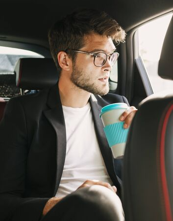 Young and attractive man with a beard and glasses drinks coffee inside a car. Business
