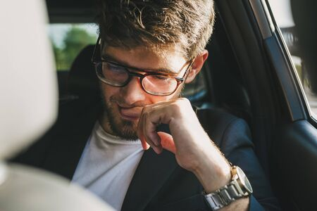 Attractive young man with a beard and glasses with a serious face reads documents inside a car. Businessman.
