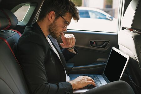 Attractive young man with a beard and glasses works with his laptop inside a car. Businessman.