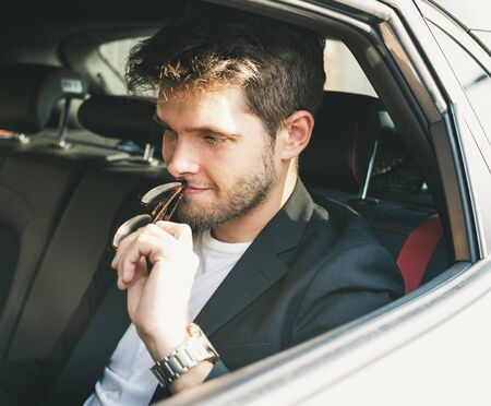 Attractive young man with a beard wearing glasses resting on his mouth is thoughtful inside a car. Businessman. Stock Photo