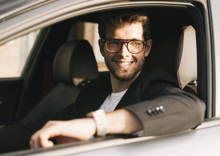 Attractive young man with a beard and glasses smiles while looking out the window of his car.