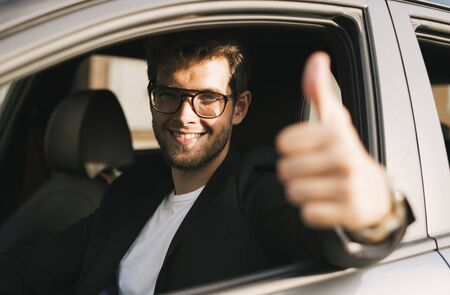 Attractive young man with a beard and glasses smiles and says ok with his hand while looking out the window of his car.