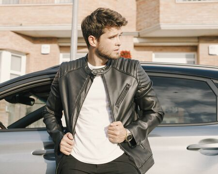 Attractive young man with a beard is leaning on his car