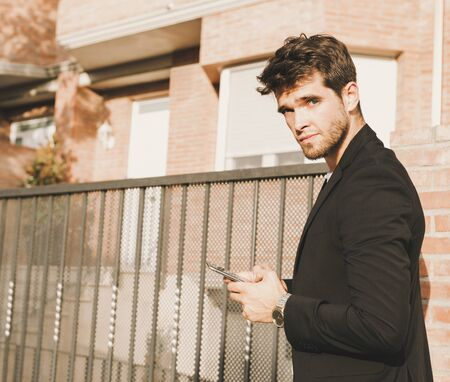 Attractive young man in a suit with a smartphone in his hand looks at camera.