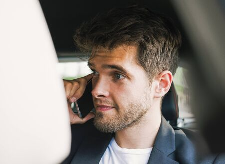 Young and attractive man with a beard speaks with his smartphone in a vehicle he does not drive. Business