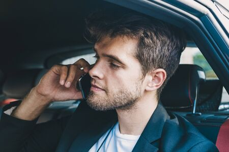 Attractive young man dressed in suit speaks with his smartphone in a vehicle he does not drive. Business