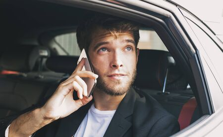 Young and attractive man with a beard speaks with his smartphone in a vehicle that does not drive and looks out the window. Business