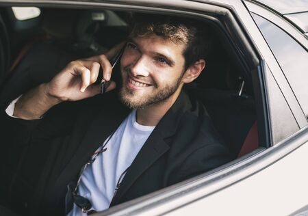 Young and attractive man with a beard smiles and talks with his smartphone in a vehicle he does not drive. Business Stock Photo
