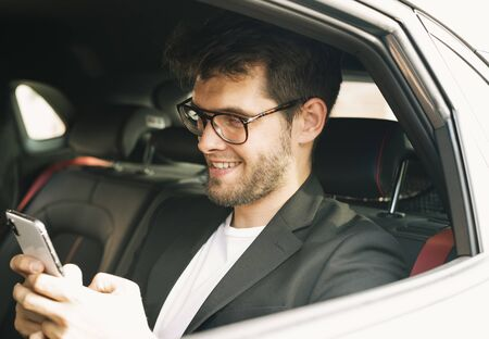 Young and attractive man with a beard and glasses smiles while using a smartphone. Business Stock Photo