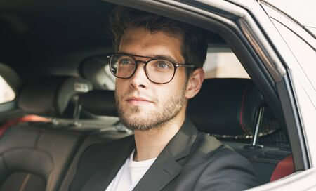 Young and attractive man with a beard and glasses smiles inside a car. Business Stock Photo