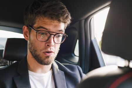 Young and attractive man with a beard and glasses with a surprised face is inside a car. Business