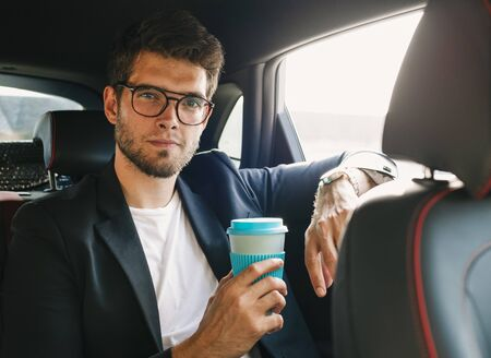 Attractive young man with a beard and glasses holds a coffee with his hand and looks at the camera. Business Stock Photo