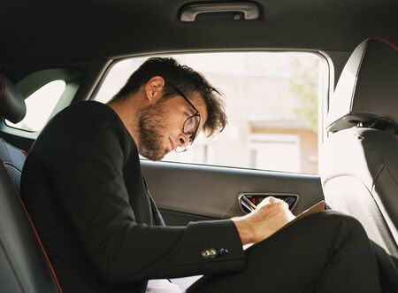 Young and attractive man with a beard and glasses works writing on some documents inside a car. Business