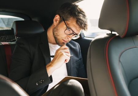 Young and attractive man with a beard and glasses works reading papers inside a car. Business