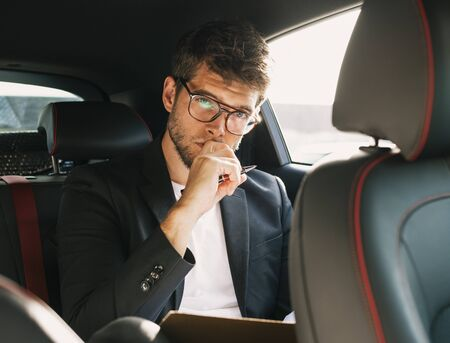 Young and attractive man with a beard and glasses works and looks at camera inside a car. Business Stock Photo