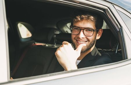 Attractive young man with a beard and glasses says ok with his finger through the window of his car. Businessman.
